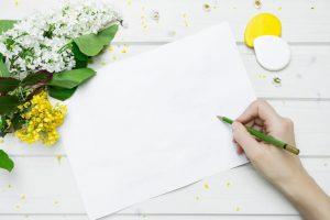Mit Blumen dekorierter Tisch, leeres Blatt und eine Hand mit grünem Stift