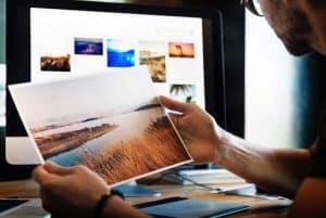 Mann, der ein ausgedrucktes, großes Foto in der Hand hält. PC Monitor mit weiteren Bildern im Hintergrund